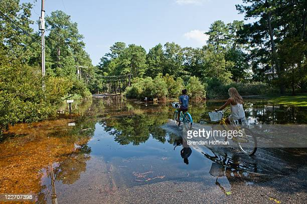 Two girls ride their bicycles through a street flooded by rain from Hurricane Irene on August 28 2011 in Virginia Beach Virginia The Category 1 storm...