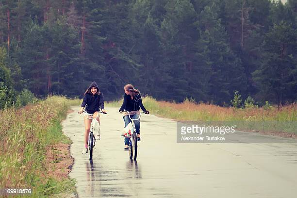 CONTENT] Two girls riding a bikes in wet weather