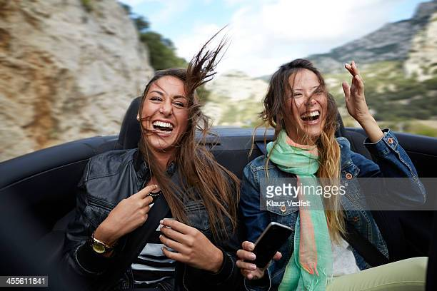 Two girls riding on backseat of car