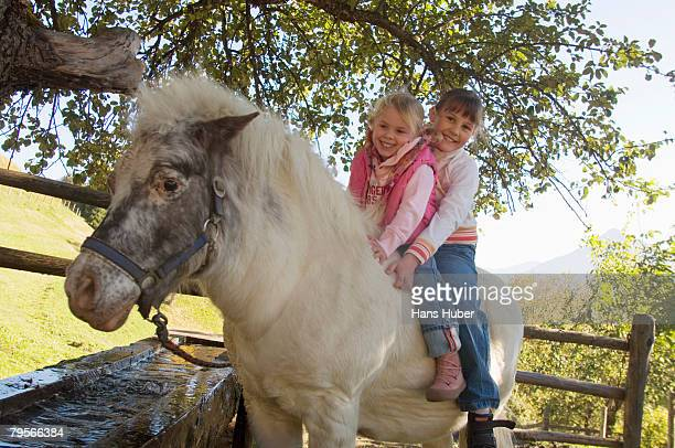 Two girls riding pony