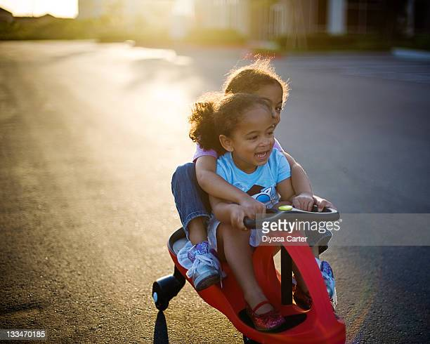 Two girls riding tandem on red push car