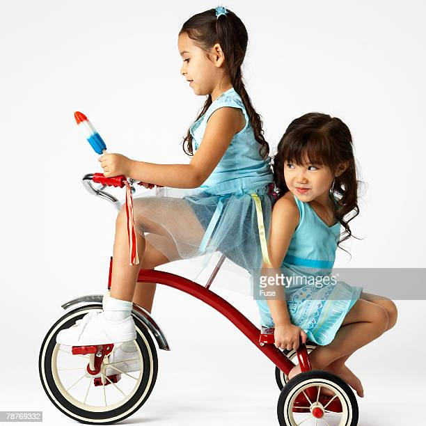 Two Girls Riding Tricycle