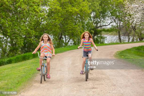 two girls riding vintage bikes on rural driveway - weathered stock pictures, royalty-free photos & images