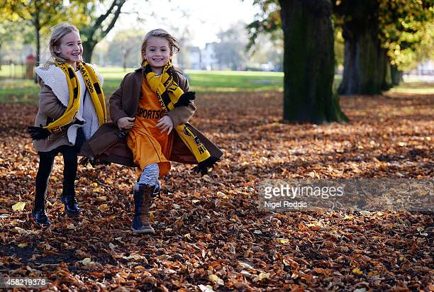 Two girls run through autumn leaves on their way to the KC Stadium ahead of the Premier League Football match between Hull City and Southampton at KC...