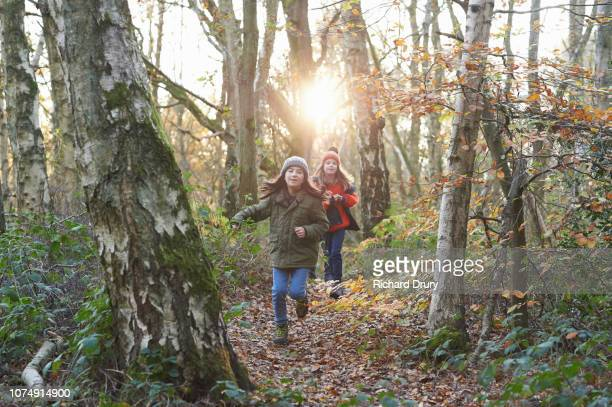 Two girls running along a footpath in Autumnal woodland
