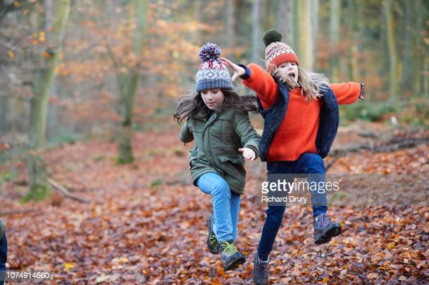 Two girls running and running and jumping in Autumnal woodland