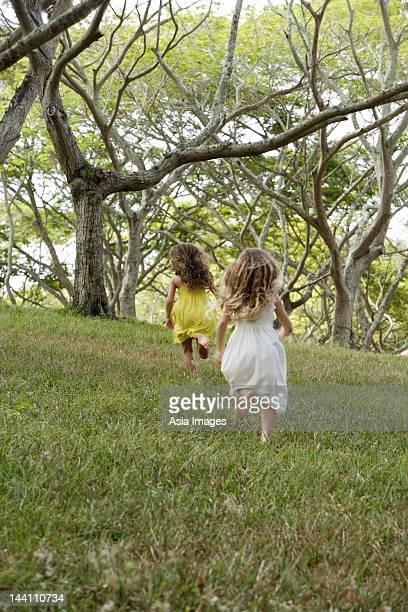 two girls running away through woods