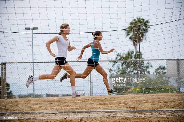 two girls running behind soccer net