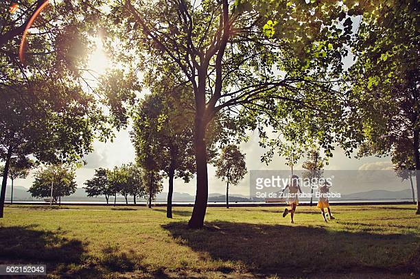 Two girls running in a park full of trees and sun