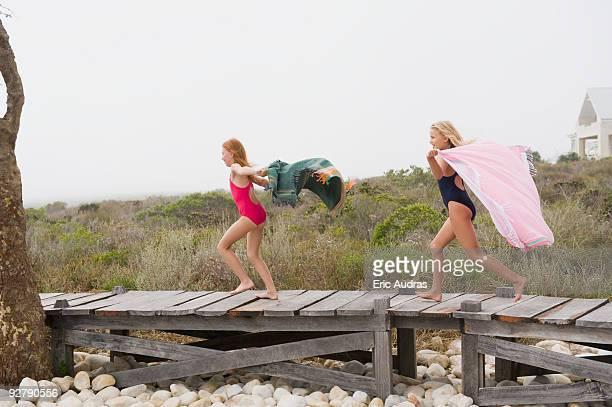 Two girls running on a boardwalk
