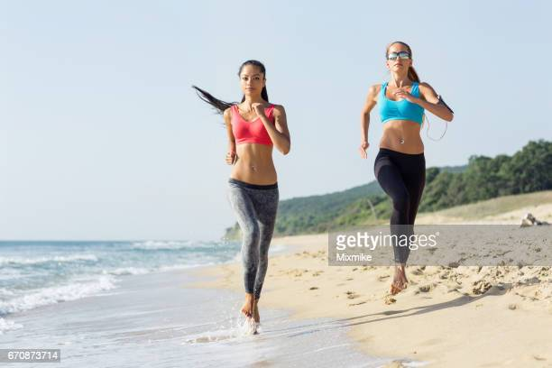 Two girls running on the beach