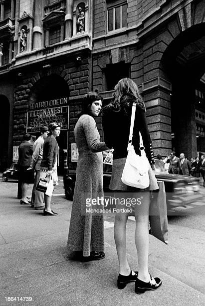 Two girls seen from back in Corso Vittorio Emanuele in Milan one of the two girls is wearing a maxiskirt the other is wearing a miniskirt the...
