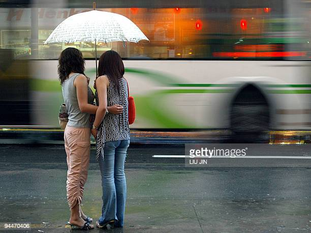 Two girls shelter under an umbrella as they wait for a taxi in Shanghai 28 June 2003 AFP PHOTO/LIU Jin