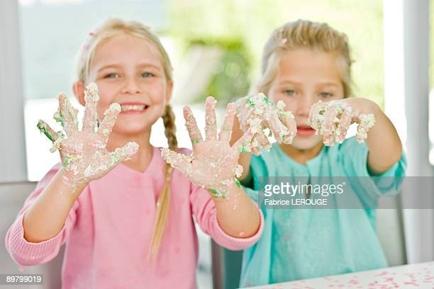 Two girls showing her hands covered with cake icing