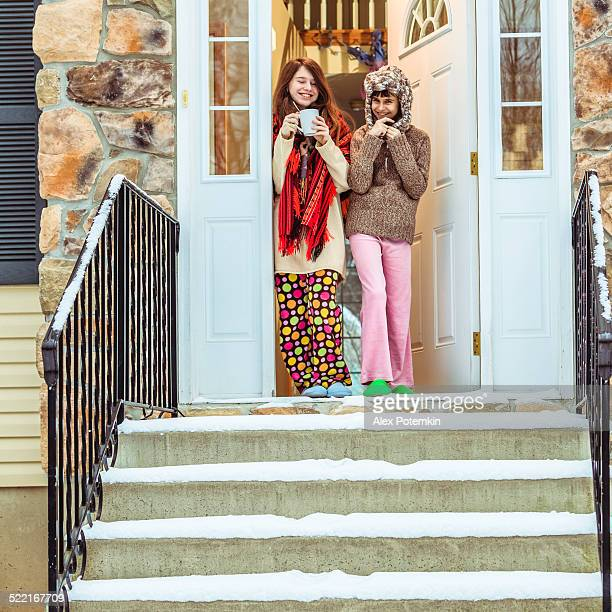 Two girls, sisters,  before contry house in winter