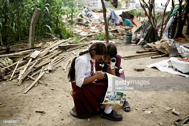 Two girls sit amongst a clearing in the Thapathali slums, which were recently demolished by the Nepalese government. In an effort to crack down on...