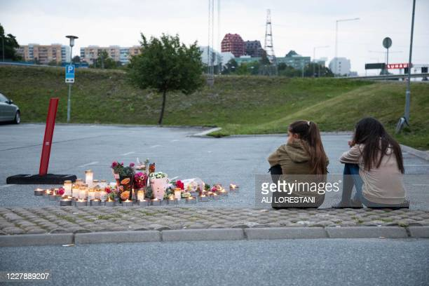 Two girls sit next to a makeshift memorial at the site where a twelve year old girl was shot near a petrol station in Botkyrka, south of Stockholm,...
