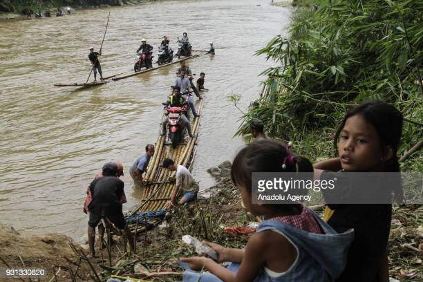 Two girls sit on the river bank as several people assist motorcyclists to pull up their vehicles onto wooden raft to cross Cisadane River in Rumpin...