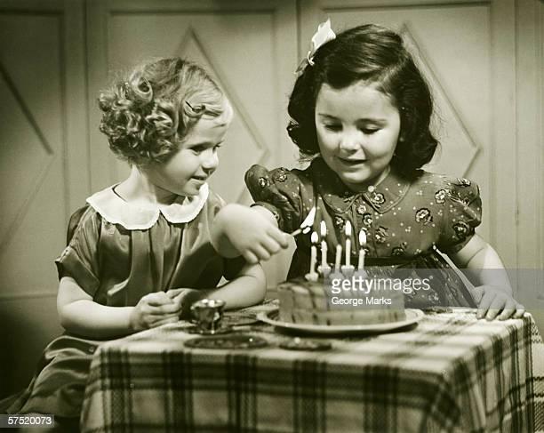 Dos chicas (3-4), (4-5) sentado en la mesa con pastel de cumpleaños.