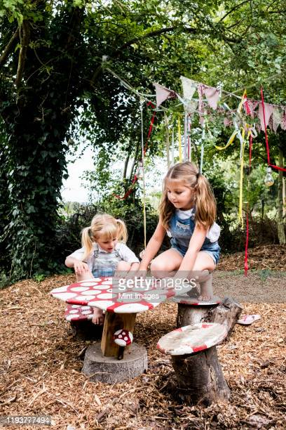two girls sitting at small wooden table in a garden, playing. - nursery school child stock pictures, royalty-free photos & images