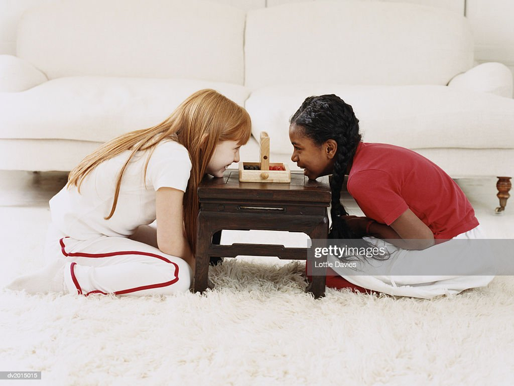 Two Girls Sitting Face to Face on a Rug, Playing a Game : Stock Photo