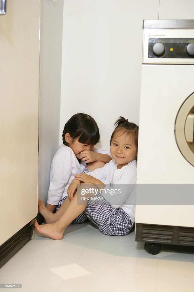 Two Girls Sitting In A Corner Near A Washing Machine High ...