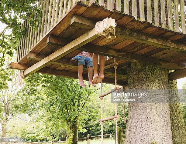 Two girls (9-11) sitting in tree house, low section, low angle view