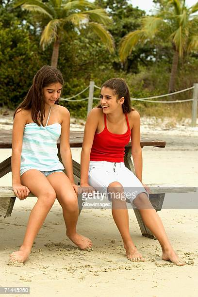 Two girls sitting on a bench at the beach
