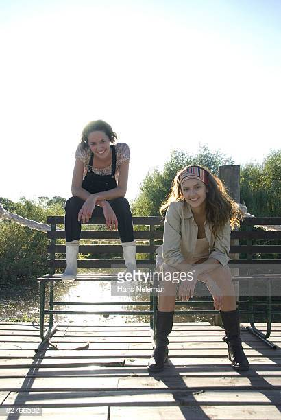 Two girls sitting on a dock