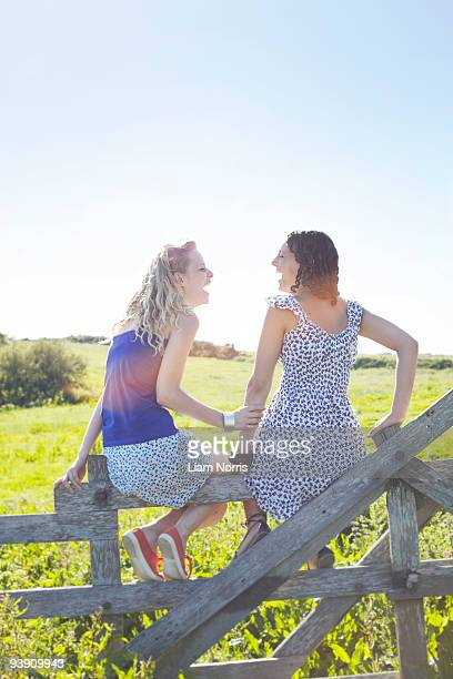 two girls sitting on a fence