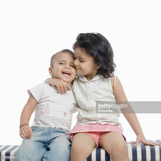 two girls sitting on an ottoman - indian girl kissing stock photos and pictures