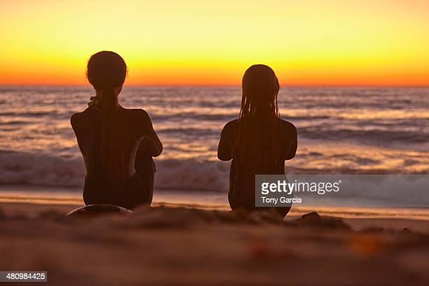 Two girls sitting on beach at sunset looking out to sea