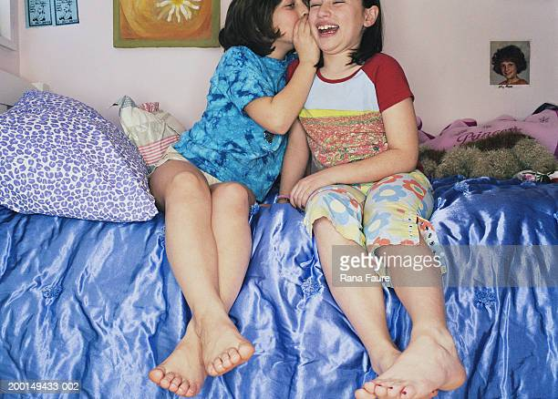 two girls (7-10) sitting on bed, one whispering to other - 8 girls no cup stock photos and pictures
