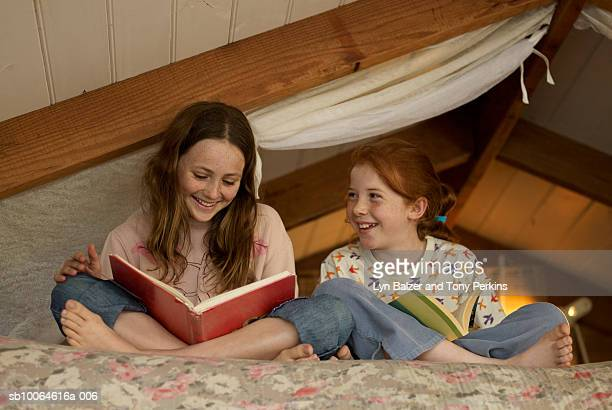 Two girls (10-11) sitting on bed, reading