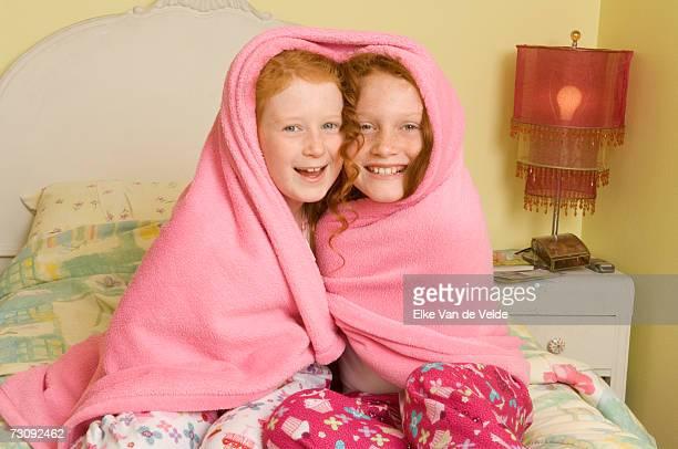 Two girls (7-10) sitting on bed, under blanket, portrait