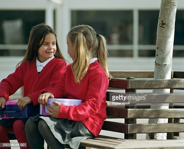 Two girls (6-8) sitting on bench holding lunch boxes