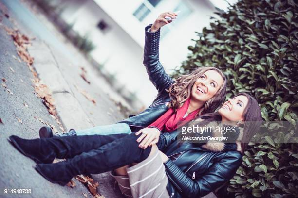 Two Girls Sitting on City Street and Making Selfie