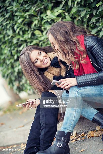 Two Girls Sitting on City Street and Using Their Smartphone