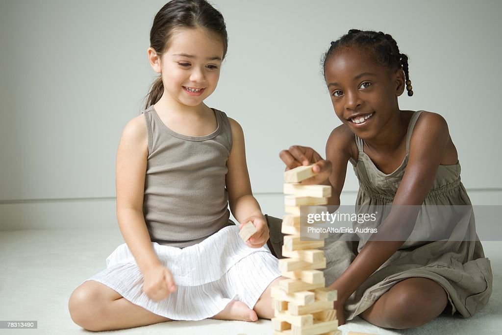 Two girls sitting on floor playing with blocks, one smiling at camera : Stock Photo