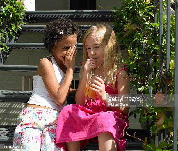 Two girls (6-8) sitting on garden steps, one whispering to other