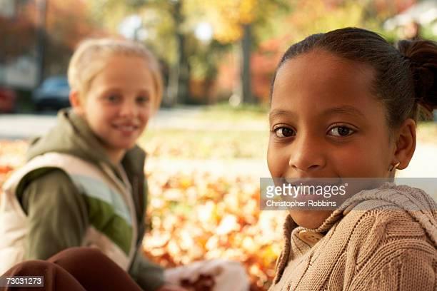 Two girls (8-9) sitting on ground in autumn park, portrait