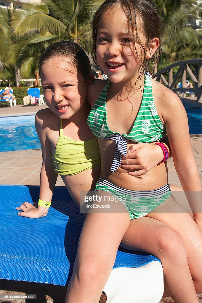 Two Girls Sitting On Lounge Chair Smiling Portrait Stock