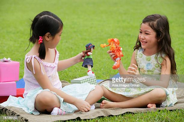 Two girls sitting on picnic blanket, playing with dolls