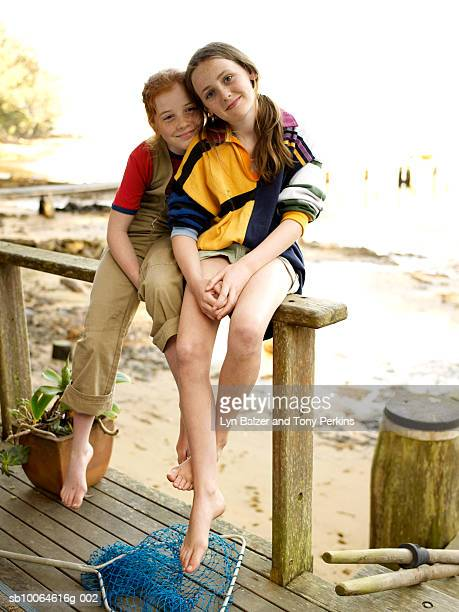 Two girls (10-11) sitting on porch railing, smiling, portrait