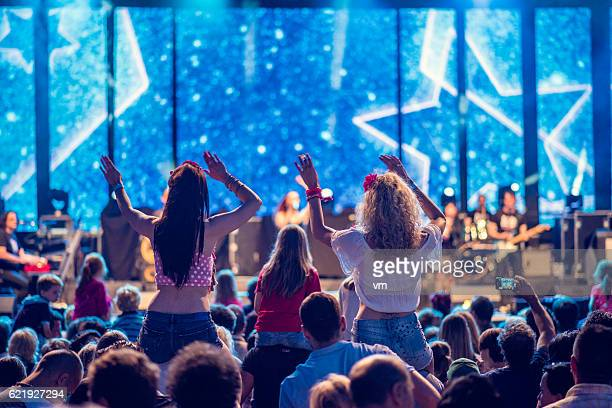 Two girls sitting on shoulders at a concert