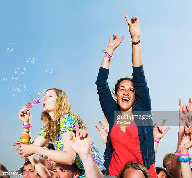 two girls sitting on shoulders in a crowd blowing bubbles - 芸能イベント ストックフォトと画像