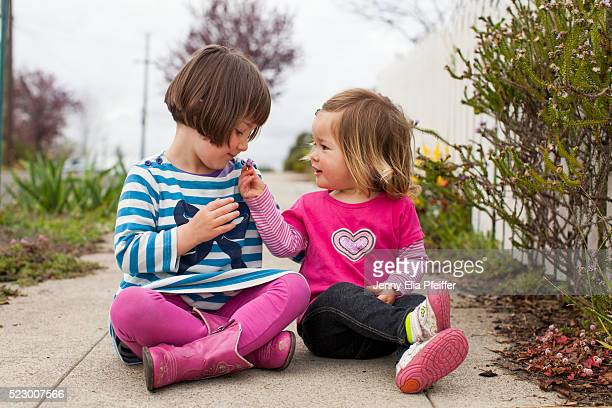 two girls (2-3, 4-5) sitting on sidewalk with flowers - sharing stock pictures, royalty-free photos & images