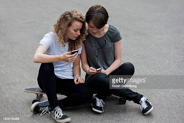 two girls sitting on skateboard looking at mobile - robin skjoldborg stock pictures, royalty-free photos & images
