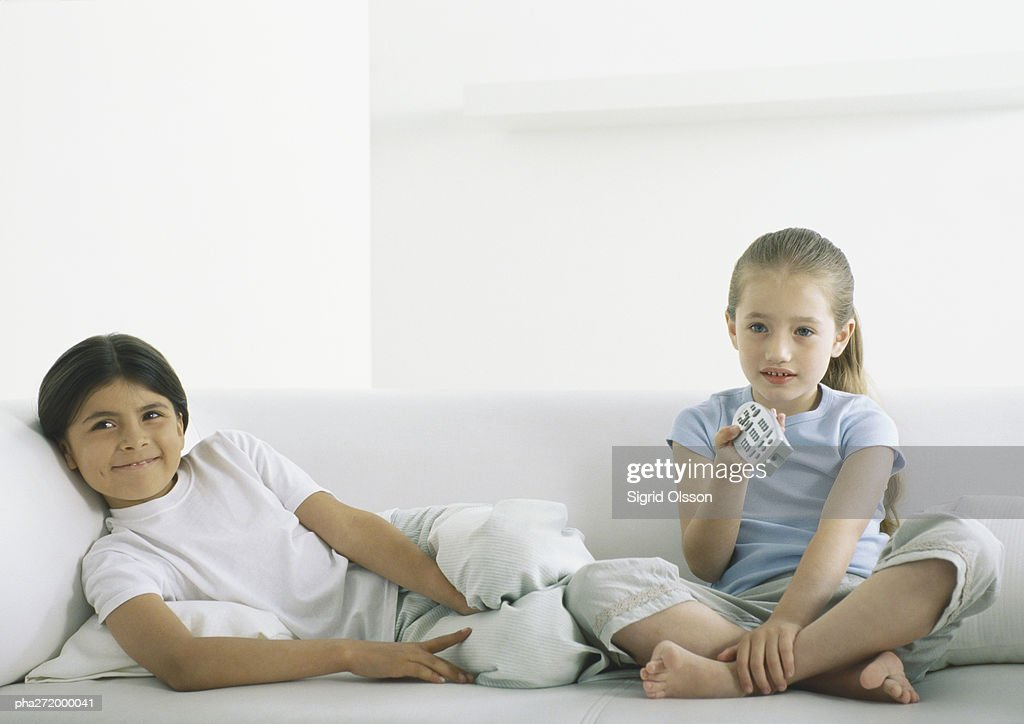 Two girls sitting on sofa, one holding remote control : Stockfoto