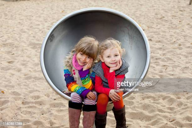 two girls sitting on spherical metal chair in park - プレンツラウアーベルグ ストックフォトと画像